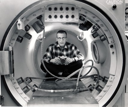 General Dynamics Astronautics photographer, Dave Mathias positioned himself inside a 33-inch wide pressure tank to capture the technician's image from the body of the tank.