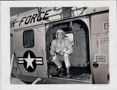 Dave Mathias sits in the side doorway of an Air Force helicopter at Forbes AFB as he goes on assignment photographing the base's Atlas missile sites in this view from 1961.