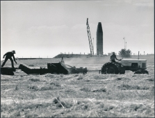 This view of two Kansas farmers baling hay with an Atlas missile erected in the background was taken in the summer of 1961 by Dave Mathias. This photo appeared in General Dynamics national corporate magazine.