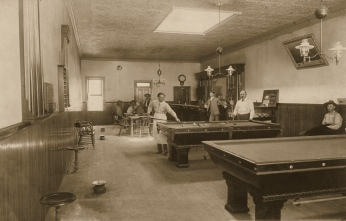 "Louis Schroeder, standing at the right hand corner of the pool table, and his brother, Gus ""Cricket"" Schroeder, standing at the bar, owned a cafe, billiard hall, and joint on Missouri Street in Alma, Kansas. Hickory Jones first job in Alma was to operate this joint at 310 Missouri Street."