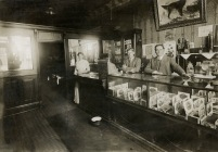 This rare interior view of the cigar counter at Jones & Co., located in the 100 block of East Main Street in Alma in 1908. Seen here from right to left are Hickory Jones, Charlie Loehr, and Emma Loehr Jones.