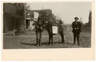 "Two men pose in the center of Newbury Avenue in Paxico for this real photo postcard from Paxico, Kansas, circa 1905. The sign on the burro's back says, ""When may we three meet again? Born in Africa."" The man standing at the right, seems to be cradling a Winchester rifle with the barrel resting on the ground by his left foot. Both men are unidentified."